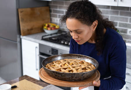 Preparation, Thanksgiving Day celebration. The young woman is sniffing the finished pie with pleasure. Making a traditional apple pie. Archivio Fotografico