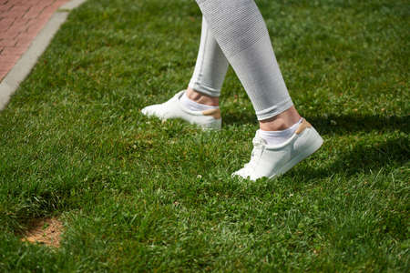 The oung woman in white sneakers on the grass. Close-up view of sneakers.