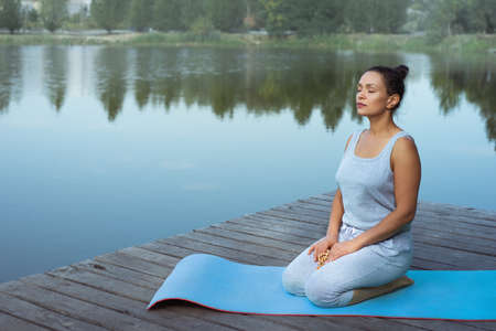 The young woman is sitting loosely on a mat by the lake holding a religious rosary with her eyes closed. Meditation in nature.