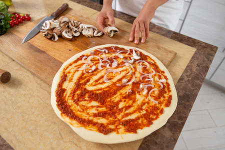 View of the chef's hands laying out the onion on top of the piece. Making vegan pizza without cheese.