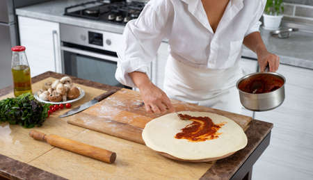 The cook spreads the tomato sauce over the piece with a spoon. The ingredients for the filling are on the table.