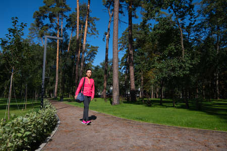The young woman with a sports bag on her shoulder walks along the path in the park. Front view. Archivio Fotografico