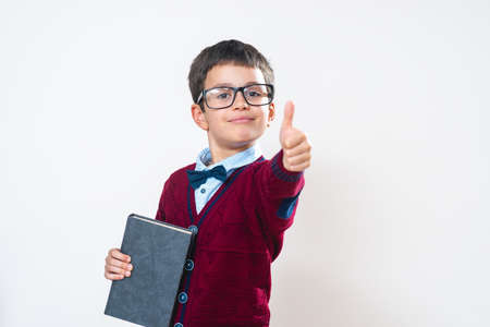 The schoolboy in a sweater with a notepad in his hands shows thumbs up to the camera. Happy child. Conceptual. Copy space.