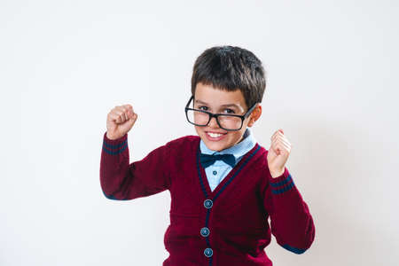 The schoolboy in a sweater and glasses rejoices. Happy child. Conceptual. Copy space.