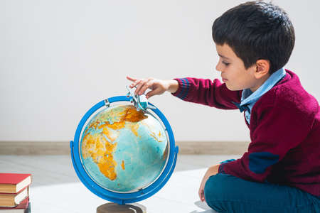 The schoolboy in a sweater sits on the floor in a pose and plays with an airplane and a globe. The illusion of travel. 免版税图像