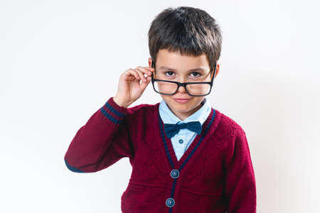 The schoolboy in a sweater looks at us over his glasses. Conceptual. Copy space.