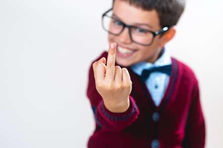 The schoolboy in a sweater shows a finger to the camera. Conceptual. Copy space. 免版税图像