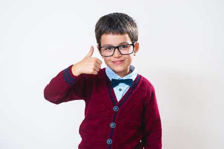 The schoolboy in a sweater and glasses smiles and shows a thumb up. Conceptual. Copy space. 免版税图像