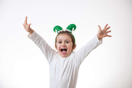 A girl with the hoop in the form of an elf's hat on her head shrietly shrieking her hands up and to the sides.