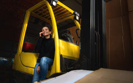 Inside a warehouse, the young woman businessman sits on the step of a yellow forklift and speaks on the phone. Logistics.