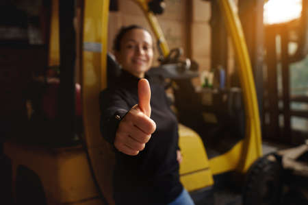 Inside the warehouse, the young woman stands in front of a yellow forklift and shows her thumbs up. Finger accent, out of focus background. 版權商用圖片