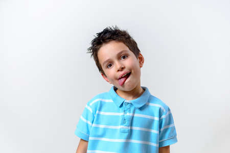 The boy in a blue t-shirt bent over his head and stuck out his tongue.