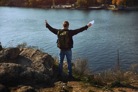 Portrait of handsome young bearded man with arms wide open. Freedom and travel adventure concept.