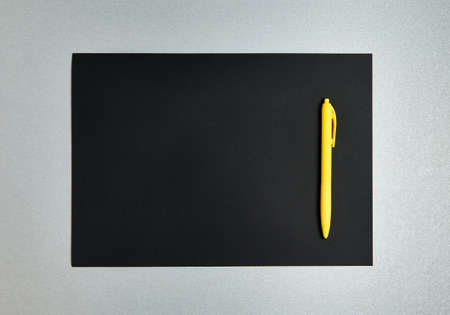 Flat lay composition with yellow pen on a black designer paper on a gray background Zdjęcie Seryjne