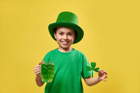 Little boy wearing leprechaun Irish hat holds a glass with green drink and a clover leaf smiles while posing on camera. Saint Patrick's Day