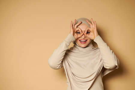 Happy smiling arab woman with covered head in hijab looking at camera through her fingers in ok gesture, imitating binoculars. The human emotions, facial expression concept. Front view.