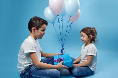 A little boy gives a gift to a little girl sitting in front of him against a background of pink and blue balloons on a blue surface