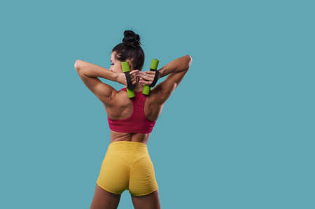Athletic woman with perfect muscular body shakes triceps, pulling dumbbells behind the muscles of the back, and stands with her back to the camera on a blue background with copy space