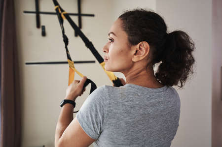 Closeup side portrait of a young woman performing functional training with fitness straps. Healthy lifestyle, workout indoors, functional training.