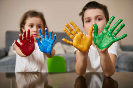 Adorable children, boy and girl, showing their hands painted in red, blue, yellow and green paints to the camera. Creative hobby Banque d'images