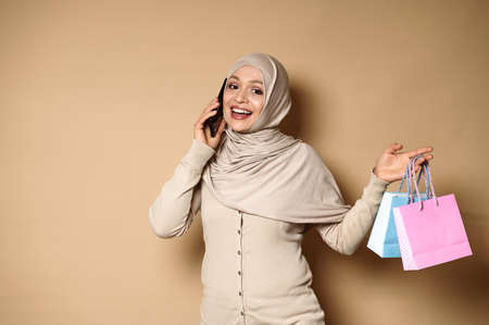Attractive Muslim Arab woman with beautiful smile in hijab holding color paper bags and talking on mobile phone. Happy events, gifts for holidays