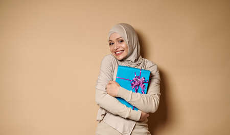 Beautiful young Arab Muslim woman hugging a gift and cutely smiling with toothy smile at camera. Beige background, copy space