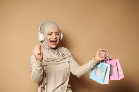 Muslim woman in hijab with headphones holding colored paper bags in her hands enjoying the upcoming religious holidays. Eid mubarak Said.