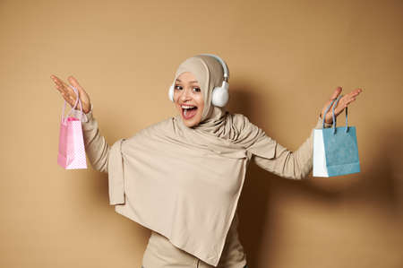 Happy Muslim woman raising arms with color bags in her hands, smiles looking at camera. Beige background with copy space