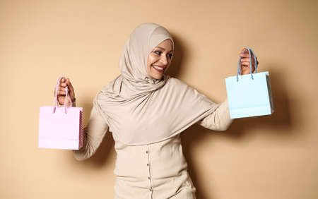 Smiling Muslim woman wearing hijab and holding blue paper bag in one hand and the pink one in the other. Shot with soft shadow on beige background with copy space