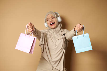 Happy woman in hijab with headphones listening to music and dancing with colored paper bags in her hands enjoying the upcoming religious holidays. Eid Mubarak Said