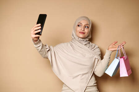 Charming Muslim woman holding blue and pink bags in one hand and a smartphone in the other, making selfie. Shopping concept, gift for events.