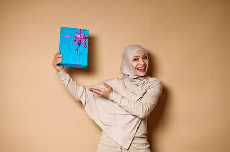 Happy Muslim woman in hijab raising her hands with a gift and presenting it to camera. Beige background, copy space. Shot with soft shadow