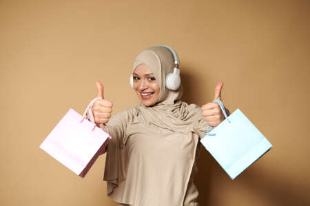 Attractive woman in hijab and headphones holding pink and blue gift paper bags in the hands and showing thumbs up, expressing happiness of upcoming religious holidays. Beige background with copy space Banque d'images
