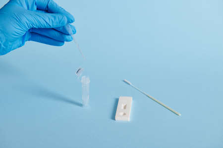 A hand in a medical glove holds a medical disposable pipette for taking a sample for express test for covid antigen, isolated on blue background with copy space