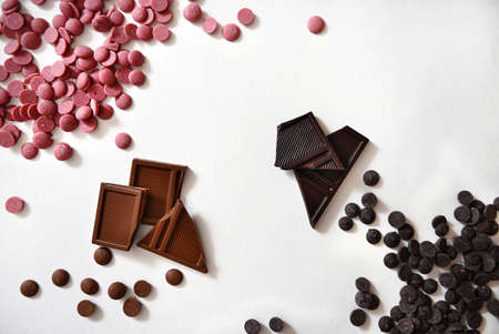 Pills of pink and dark chocolate scattered in the corners of a white surface and a chocolate bar in the middle of a white background with copy space