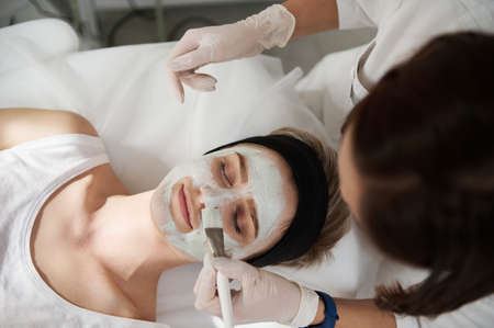 High angle view of a woman receiving cosmetic procedure in SPA center. Moisturizing face mask . Facial skin treatment. Professional body and face skin care in a modern equipped spa salon Foto de archivo