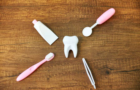 Flat Lay composition with toy dental tools for oral care. A toy white tooth, a toy dental mirror, forceps, toothpaste and toothbrush on a wooden background. Oral care concept for children Stock Photo