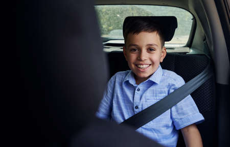 Shot through the driver seat of a smiling school boy fastened with seatbelt while travelling by car in safety child car seat Reklamní fotografie