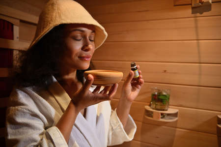 Beautiful serene Latin-American woman enjoys the aroma of essential oil in a wooden mortar while steaming in a wooden sauna. Close-up portrait