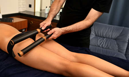 Ayurvedic bamboo stick massage performed by professional masseur on woman's body in wellness spa resort