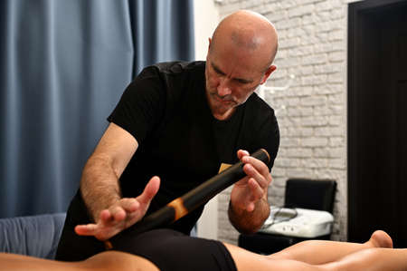 Unrecognizable woman receiving anti-stress massage with bamboo sticks. Body rejuvenating concepts in the wellness spa clinic