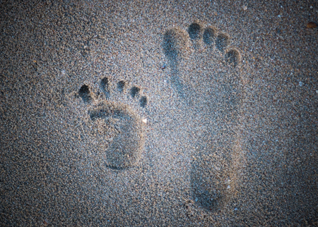 Adult footprint beside child footprint on the tropical beach.Footprints in the sand at sunset. Beautiful sandy tropical beach with sea waves. Stockfoto