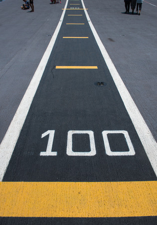 Number  100  on white and yellow runway. Takeoff runway and runway aircraft carrier on battleship. Public area.