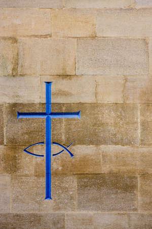 christian fish: Grabado de una cruz y el pescado en un muro de piedra