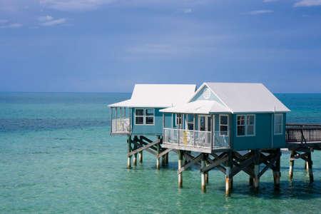 stilts: Hotel cabanas standing on stilts in the sea Stock Photo