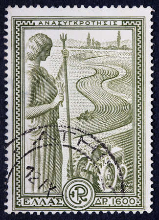 A postmarked Greek stamp showing a statue overlooking an agricultural field photo