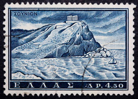 A postmarked Greek stamp showing a cliff with an ancient structure on top photo
