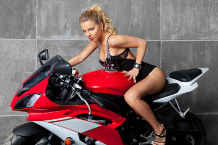 Sexy blonde  with perfect body on red sportbike
