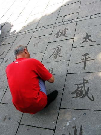 ephemeral: Street art: Ephemeral Chinese ideograms painted with water.