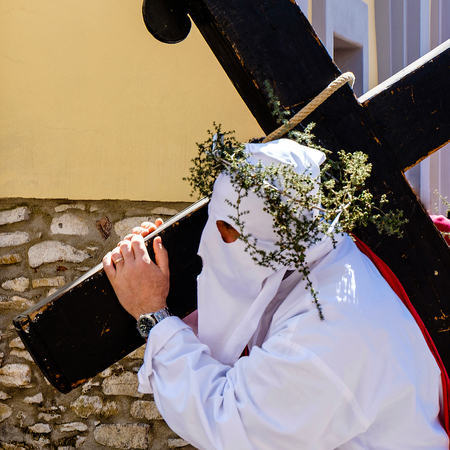 Way of the Cross in a southern Italian town. White hooded man with black cross Stock Photo